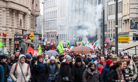 STRASBOURG, FRANCE - MAR 22, 2018: CGT General Confederation of Labour workers with placard at demonstration protest against Macron French government string of reforms - smoke grenade in background