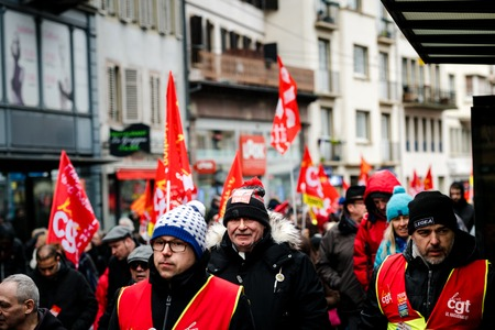 STRASBOURG, FRANCE - MAR 22, 2018: CGT General Confederation of Labour workers with placard at demonstration protest against Macron French government string of reforms - group of people closing street near tramway station
