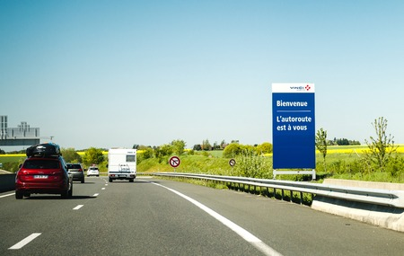 FRANCE - MAY 5, 2016: Cars driving fast on French highway with signage Welcome, the highway is yours - toll road operated by Vinci