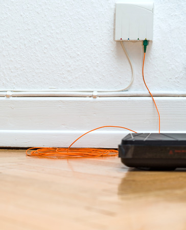 Detail of Fiber optic installation at home with obsolete CATV and new FTTH fiber outlets and internet receiver on parquet floor