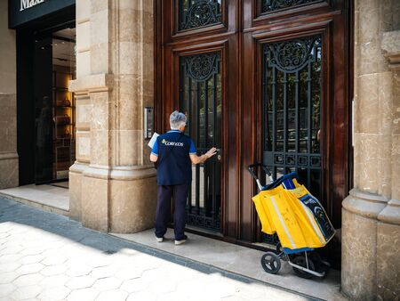 BARCELONA, SPAIN - JUN 1 2018: Rear view of female worker mailwoman delivering mail ring on the doorbell at large door in central Barcelona to distribute a letter and parcel - wearing Correos jacket
