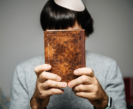 Jewish male wearing Kippah praying reading Bi-lingual Hebrew French mahzor prayer book from 1920 used on the High Holy Days of Rosh Hashanah and Yom Kippur holding book in front of the face.