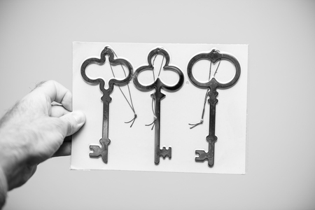 Man holding against white background a set of three vintage ancient keys black and white Stok Fotoğraf