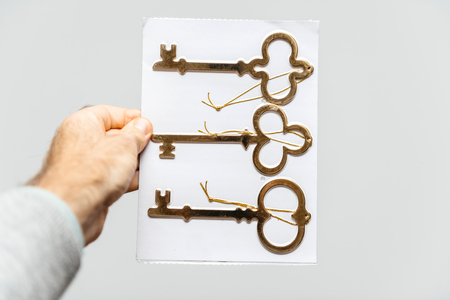 Man holding against white background a set of three vintage ancient gold keys - vertical holding Stok Fotoğraf