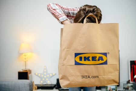 PARIS, FRANCE - DEC 2, 2018: Casual dressed woman holding big paper IKEA bag full with merchandise from the famous swedish furniture retailer - searching inside the bag
