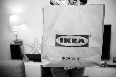 PARIS, FRANCE - DEC 2, 2018: Elegant French woman holding big paper IKEA bag full with merchandise from the famous swedish furniture retailer - black and white Redactioneel