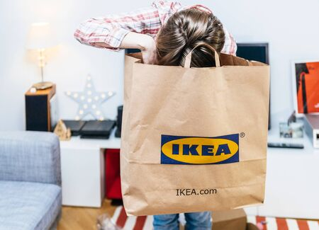 PARIS, FRANCE - DEC 2, 2018: Elegant French woman holding big paper IKEA bag full with merchandise from the famous swedish furniture retailer - head in the bag searching objects