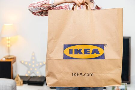 PARIS, FRANCE - DEC 2, 2018: Elegant French woman presenting big paper IKEA bag full with merchandise from the famous swedish furniture retailer