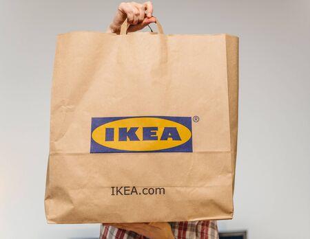 Paris, Frankrijk - 2 Dec 2018: Elegante Franse vrouw met grote papieren Ikea-tas vol met koopwaar van de beroemde Zweedse meubelhandelaar - die voor haar houdt Redactioneel