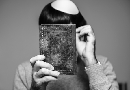 Jewish male wearing Kippah praying mahzor prayer book from 1920 used on the High Holy Days of Rosh Hashanah and Yom Kippur - black and whtie