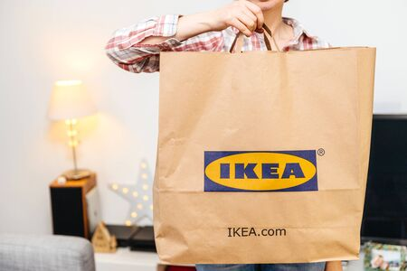 PARIS, FRANCE - DEC 2, 2018: QWoman with big paper IKEA bag full with merchandise from the famous swedish furniture retailer with advertising to its ikea.com website