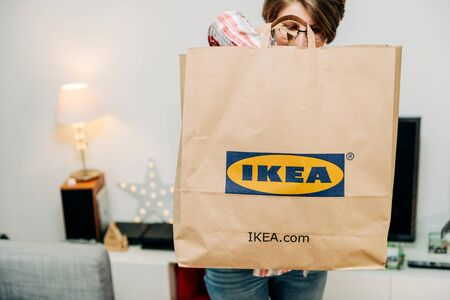 PARIS, FRANCE - DEC 2, 2018: Elegant French woman searcing for presents objects in big paper IKEA bag full with merchandise from the famous swedish furniture retailer