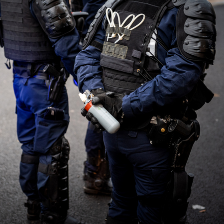 French Police officers securing the zone in front of the yellow vests movement protesters on Quai des Bateliers street woman officer with tear gas bottle ready to use it - square image,