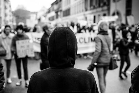 Silueta mirando a la multitud marchando en el centro de Estrasburgo en la protesta nacional Marche Pour Le Climat en blanco y negro Foto de archivo