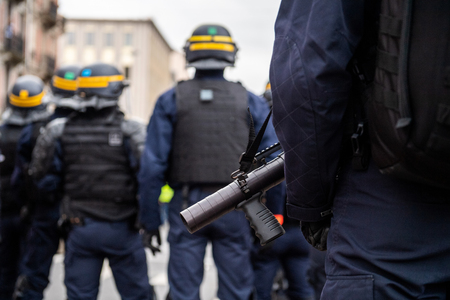 French Police officers securing the zone in front of the yellow vests movement protesters focus on gas smoke tear grenade gun Standard-Bild - 122881138