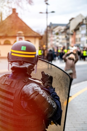 Rear view of police officer wearing helmet and shield securing the zone in frong of the Yellow vests movement gilets jaunes protesters on Quai des Bateliers street .