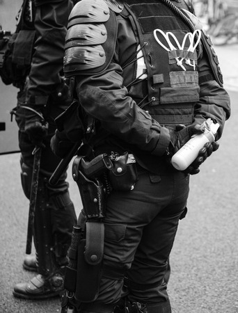French Police officers securing the zone in front of the yellow vests movement protesters on Quai des Bateliers street woman officer with tear gas bottle ready to use it - black and white. Standard-Bild - 122881227