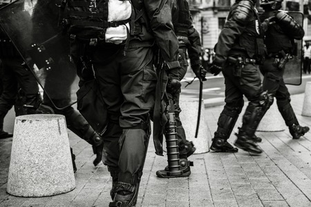 Rear view of police officers securing the zone in front of the Yellow vests movement protesters on Quai des Bateliers street detail on their guns, rifles, baton, gas tear guns, Foto de archivo