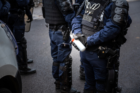 French Police officers securing the zone in front of the yellow vests movement protesters on Quai des Bateliers street woman officer with tear gas bottle ready to use it focus on bottle,