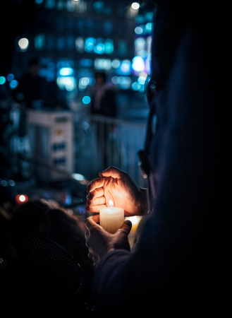 Woman holding candle at vigil with multiple light candles flowers and messages for the victims of terrorist Cherif Chekatt at Christmas Market