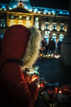 Woman holding candle protecting from wind at vigil with multiple light candles flowers and messages for the victims of terrorist Cherif Chekatt at Christmas Market