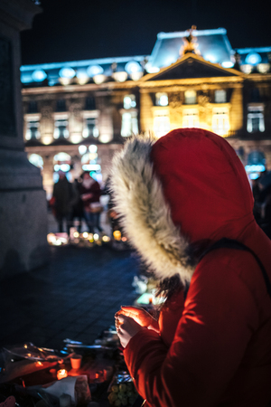 Large crowd of people mourners gathered near General Kleber statue to attend a vigil with multiple light candles flowers and messages for the victims of terrorist Cherif Chekatt at Christmas Market.