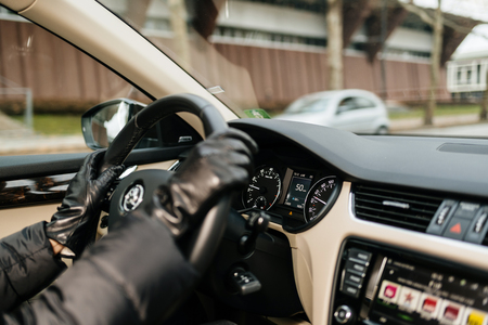 STRASBOURG, FRANCE - DEC 26, 2018: Woman driving Skoda Octavia Czech car wearing leather gloves in the center of Strasbourg, France with 50 km per hour Фото со стока