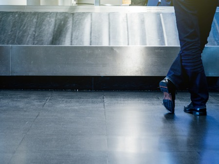 Rear view of a man with crossed legs waiting for luggage at the conveyor belt