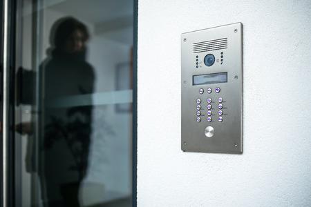 Silueta de mujer preparándose para entrar en casa de lujo moderno con foco en el interfono digital de la puerta Foto de archivo