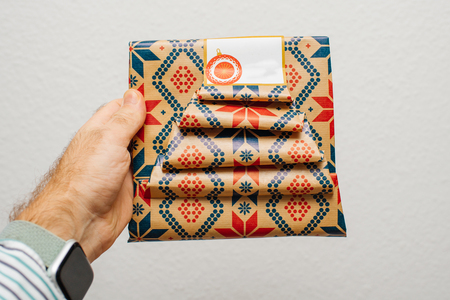 Man hand holding against white background gift wrapped in festive paper - delicate design handmade packaging