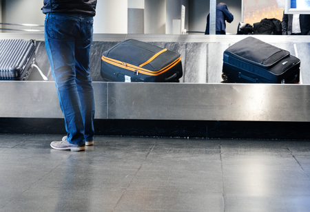 Rear view of a man preparing to take luggage from the conveyor belt in modern Airport Imagens