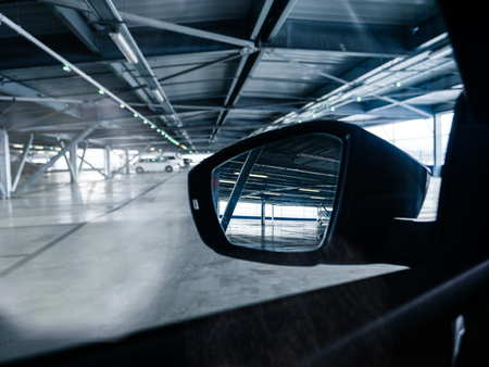 Rear view mirror - driver point of view inside the large empty parking - concept of security and safety