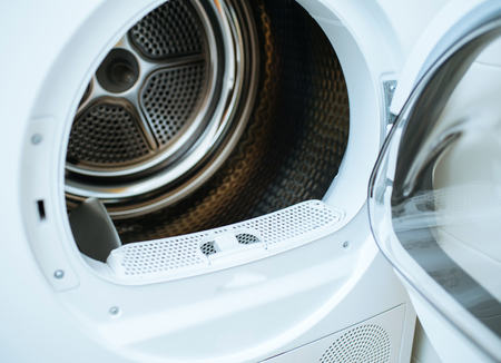 Open door of a modern new front-load clothes dryer appliance machine with empty tumble
