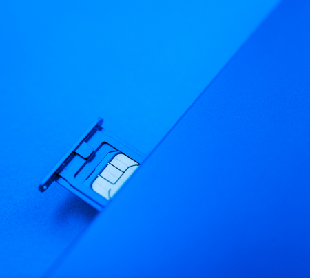 Micro SIM card subscriber identity module inside new smartphone telephone mobile device against blue background Foto de archivo