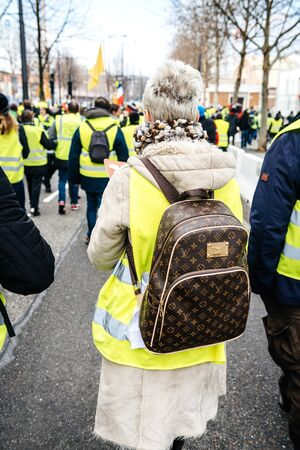 STRASBOURG, FRANCE - FEB 02, 2018: Rear view of adult woman with Louis Vuitton backpack during protest of Gilets Jaunes Yellow Vest manifestation anti-government demonstrations on Boulevard de Dresde