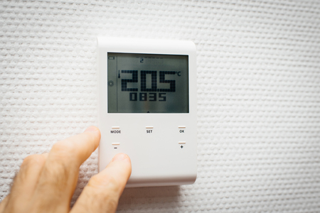 Mannhand, die im Inneren des Hausbüros die Temperatur mit dem Wandregler mit digitaler Feuchtigkeits-, Temperatur- und Klimaeinstellung steuert Standard-Bild