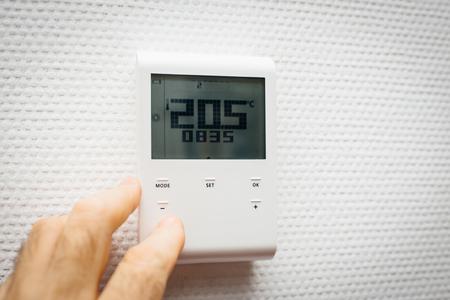 Mano de hombre controlando en el interior de la oficina de la casa la temperatura usando el regulador de pared con humedad digital, temperatura, ajuste de clima Foto de archivo