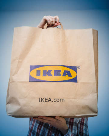 Paris, France - Dec 2, 2018: Woman presenting IKEA ecological reusable bag with multiple merchandise inside - shopping at the furniture and home decoration supermarket store