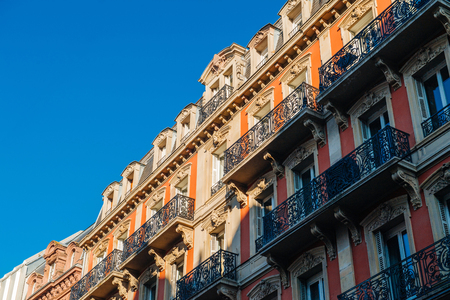 Majestic balconies view from below of French Haussmannian apartment building with clear blue sky early in the morning - real estate property management luxury in France