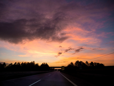 Driving on german autobahn on a beautiful sunset with magenta purple and ornage tones