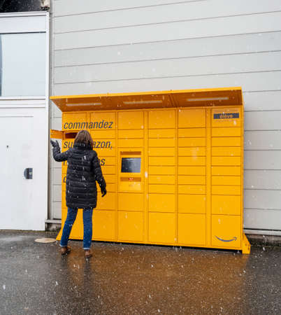 Strasbourg, France - Feb 8, 2018: Young woman Amazon Locker the self-service parcel delivery service station near Auchan supermarket open the door look inside to retrieve cardboard box