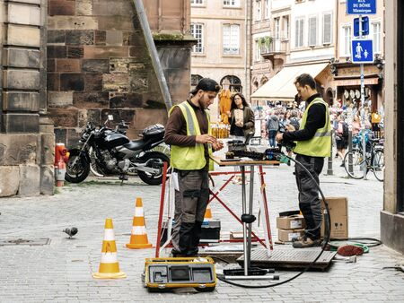 Paris, France - June 13, 2018: Team working near open sewage manhole hole - internet provider company working on implementation of fiber optic cables in French city public internet network infrastructure Éditoriale