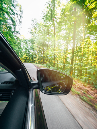 Vertical image of new modern car driving fast into forest with tall trees and empty mountain highway escaping running evading from all concept concept