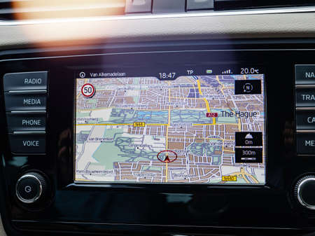 THE HAGUE, NETHERLANDS - AUG 19, 2018: Modern car transportation interior with detail of new GPS tablet inside of car dashboard while navigating in city of Tfe Hague