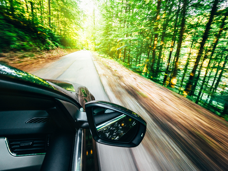 new modern car driving fast into forest with tall trees and empty mountain highway escaping running evading from all concept concept Фото со стока