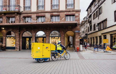 STRASBOURG, FRANCE - MAR 15, 2019: La Poste courier delivery riding electric bike with cargo trailer containing letters and parcel 新聞圖片