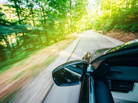 Horizontale Ansicht eines neuen modernen Autos, das schnell in den Wald fährt, mit hohen Bäumen und leerer Bergautobahn, die allen Konzeptkonzepten ausweicht