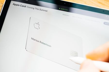 Paris, France - Mar 27, 2019: Man POV at iPad Pro tablet reading on Apple.com website about new Apple Card pointing with Apple Pencil to Titanium Mastercard