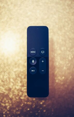 Paris, France - 25 Mar 2019: Modern sparkle holiday fade background with remote control of Apple TV 4k player with Siri assistant browsing Apple TV plus subscription film series documentaries