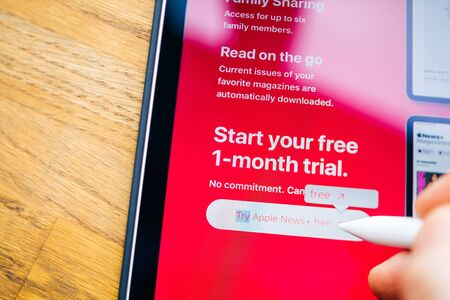Paris, France - Mar 27, 2019: Apple News Plus demo website on iPad Pro showing Start your free 1 month trial a service which gives users access to more than 300 magazines for a monthly payment